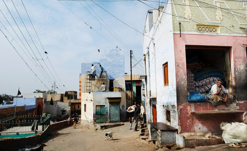 Illustrasjonsfoto: Livets teater spilles på gatene i India. Hver dag er en ny forestilling.  Et ordnet kaos av strømledninger bryter opp den blå himmelen. En av husveggene går i ett med skyene. På taket står to menn og stryker maling. Det kan se ut som de har blandet ut dagens himmelnyanser i lyseblått og hvitt. Til forveksling ligner det på malingen av teaterkulisser, men det er bare livets teater. Slik det spilles på gatene i India hver dag. Byen Bikaner i Rajastan er som indiske byer flest med et levende gateliv av absurditeter og fascinerende forestillinger.  Foto: Erlend Berge
